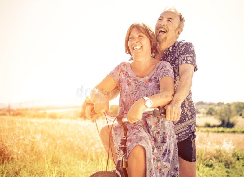 Pares de la Edad Media que van para un paseo con la bicicleta imagenes de archivo