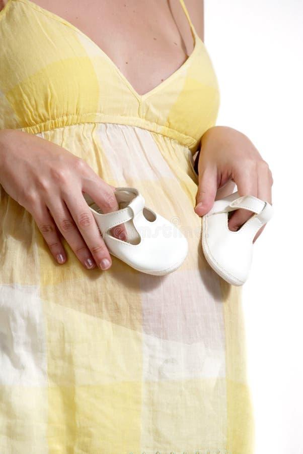 Pares de la explotación agrícola de la mujer embarazada de zapatos blancos imagen de archivo libre de regalías