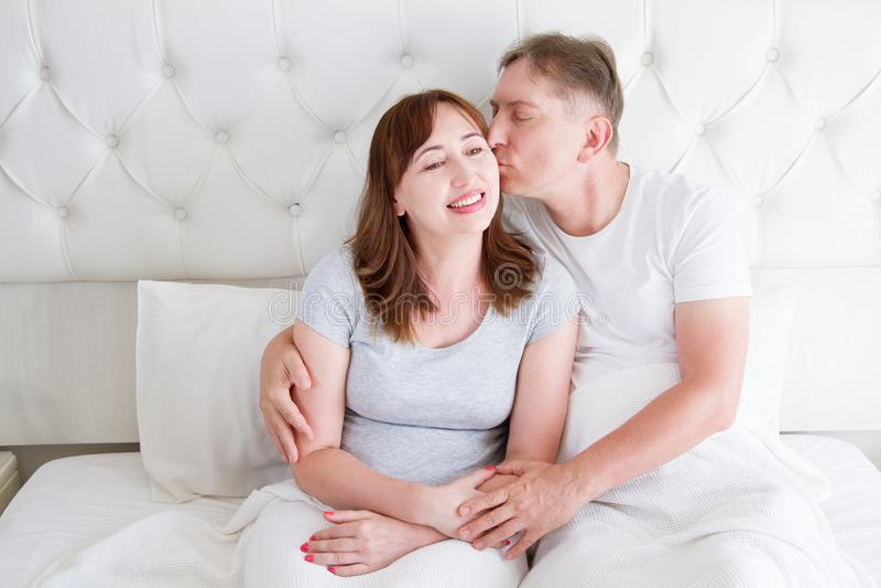 Pares de la familia de la Edad Media en el dormitorio blanco en cama Esposa del beso del marido Amor y romance Lazo sano imagenes de archivo