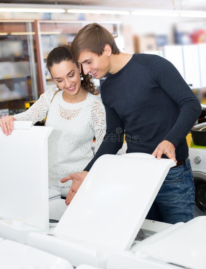 Pares de la familia que compran la nueva lavadora de ropa en tienda de dispositivo imágenes de archivo libres de regalías