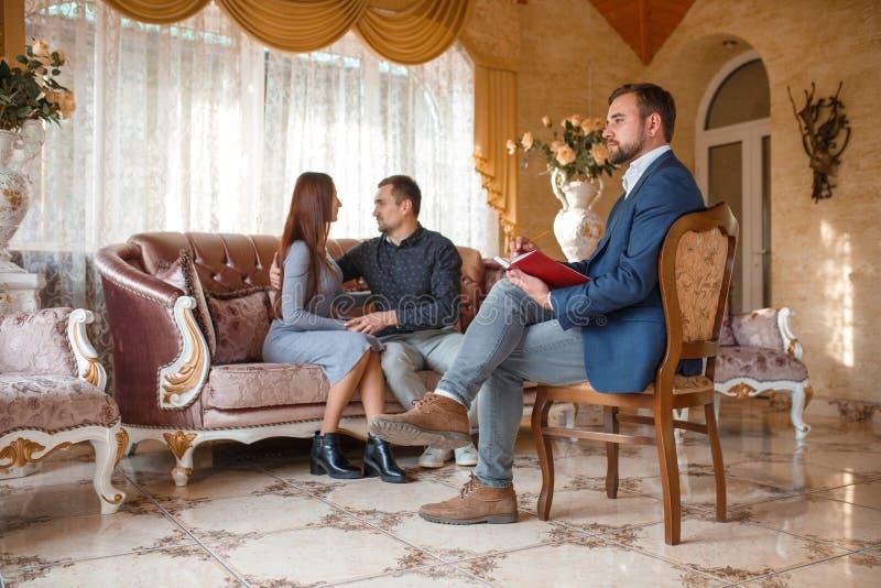 Pares de la familia que se abrazan en el sofá en una recepción con un psicólogo fotografía de archivo