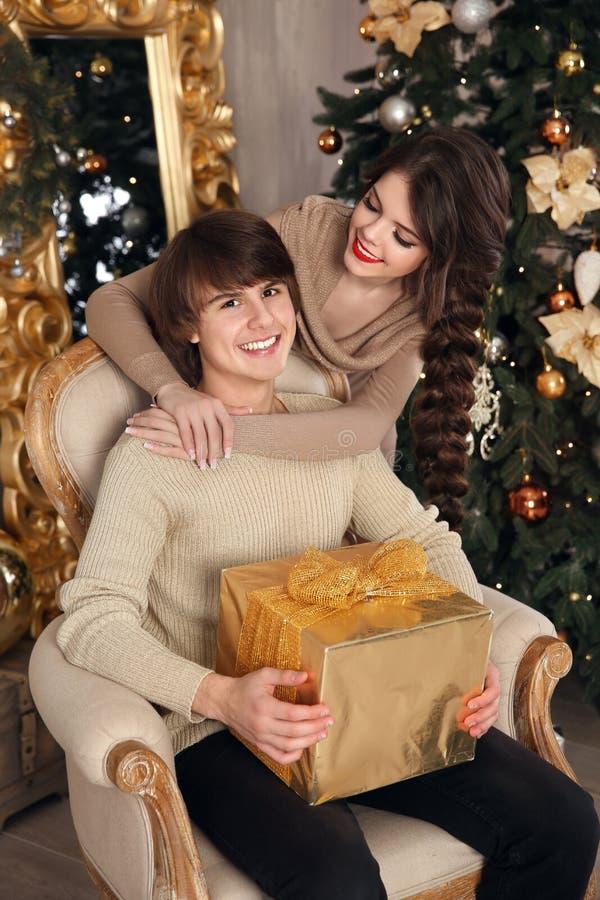 Pares de la feliz Navidad en amor Muchacha morena joven que abraza la mano imagen de archivo libre de regalías