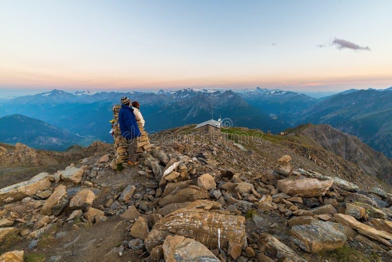 Pares de la gente que mira la salida del sol sobre pico de montaña de Mont Blanc 4810 m ` Aosta de Valle d, aventuras italianas d imágenes de archivo libres de regalías