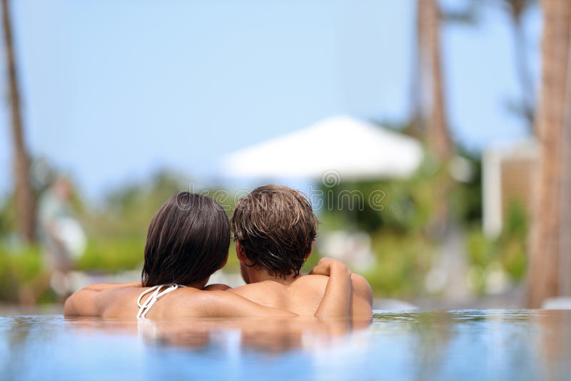 Pares de la luna de miel que relajan junto - la piscina imagen de archivo libre de regalías