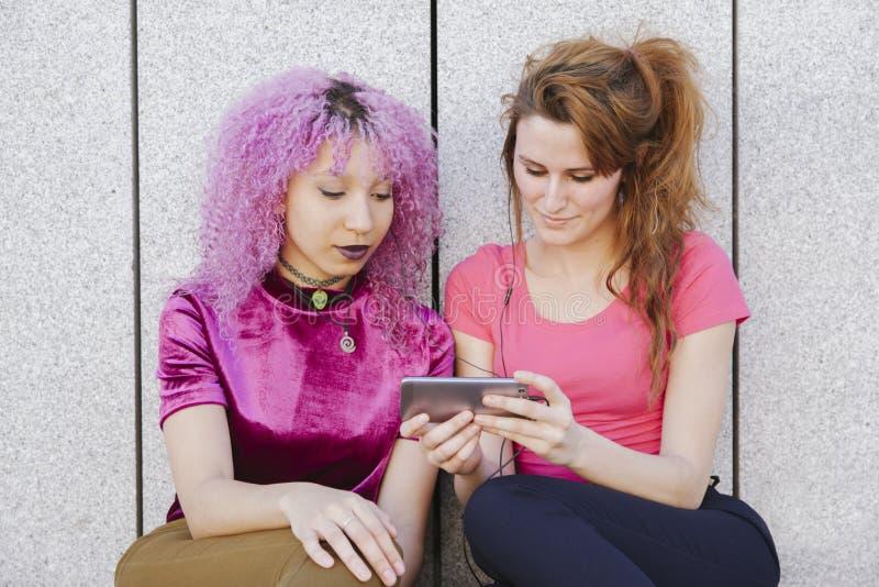 Pares de la mujer adolescente que comparten los auriculares y que escuchan la música encendido foto de archivo