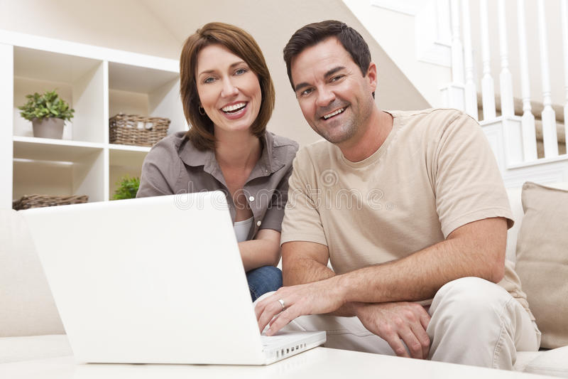 Pares de la mujer del hombre usando el ordenador portátil en el país imagenes de archivo