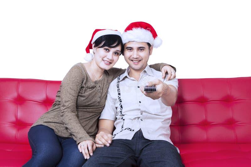 Pares de la Navidad que ven la TV el sentarse en el sofá imagen de archivo