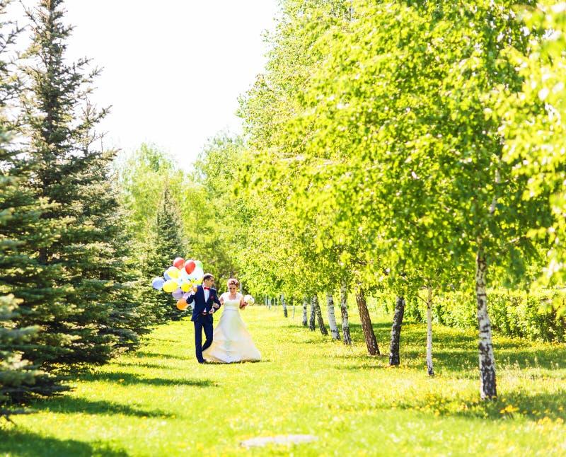Pares de la novia y del novio con los globos Recienes casados con los globos al aire libre fotografía de archivo libre de regalías