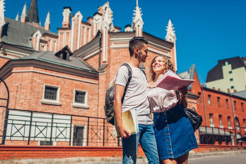 Pares de la raza mixta de los estudiantes universitarios que caminan por la universidad con los cuadernos El estudiar del hombre  fotos de archivo libres de regalías