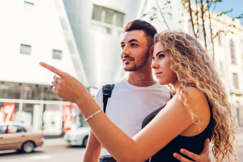 Pares de la raza mixta de los turistas que caminan en ciudad El hacer compras que va del hombre árabe y de la mujer blanca imagenes de archivo