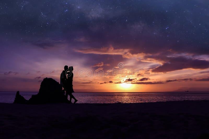 Pares de la silueta que se besan en la playa con millón de galaxias de las estrellas y el cielo púrpura imágenes de archivo libres de regalías