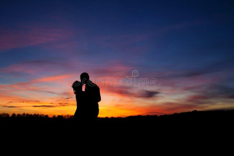 Pares de la silueta que se besan sobre fondo de la puesta del sol foto de archivo