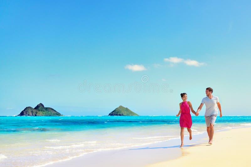 Pares de las vacaciones de Hawaii que caminan en la playa de la turquesa foto de archivo libre de regalías