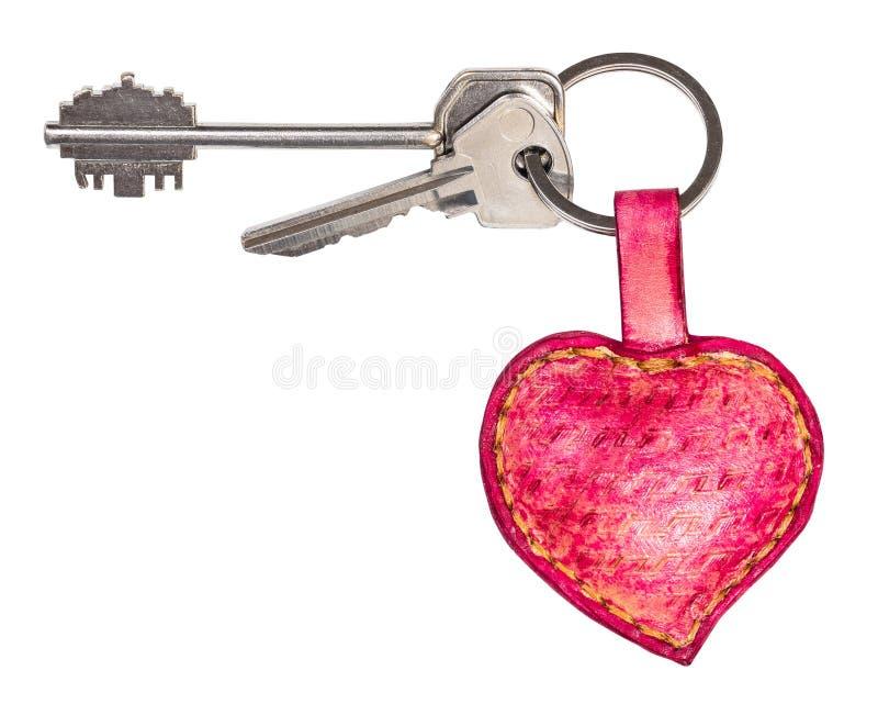 Pares de llaves en llavero en forma de corazón de cuero rosado imagen de archivo libre de regalías