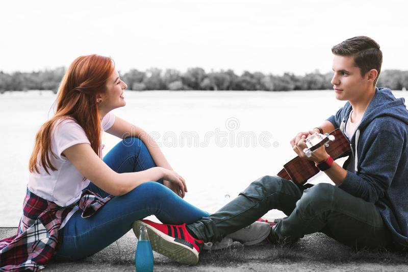 Pares de los adolescentes de emisión felices que disfrutan de la tarde agradable con la guitarra cerca del río fotos de archivo libres de regalías