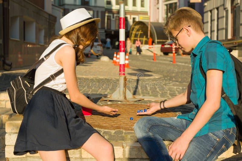 Pares de los adolescentes que relajan y que juegan un dado que lanza del juego de mesa, fondo de la calle de la ciudad foto de archivo libre de regalías