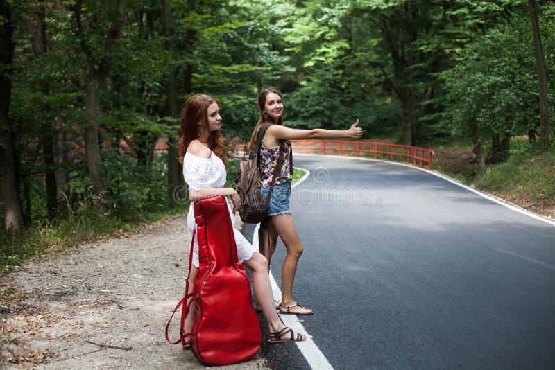 Pares de los amigos en un viaje por carretera que hacen autostop con la mochila y la guitarra fotografía de archivo