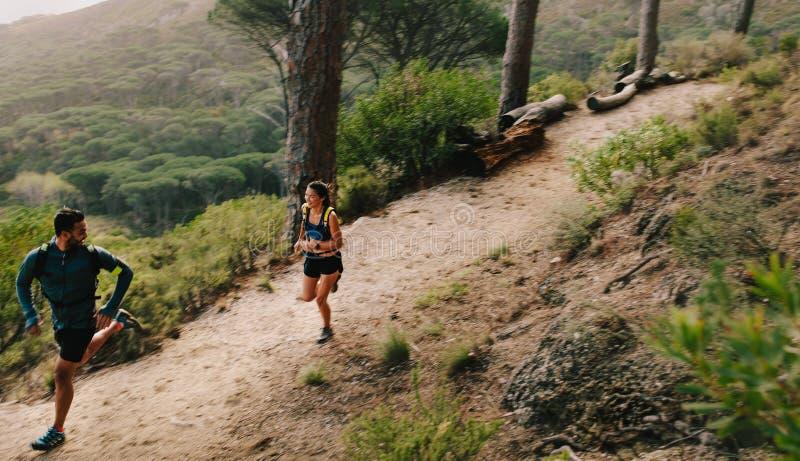 Pares de los atletas del ajuste que corren en la trayectoria de la montaña fotos de archivo libres de regalías