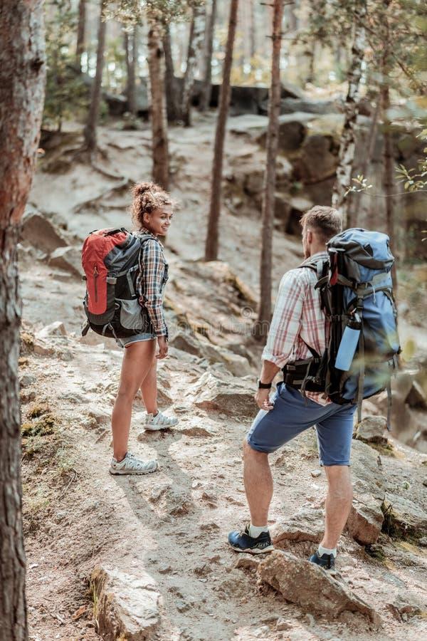 Pares de los backpackers que llevan las camisas ajustadas y las zapatillas de deporte que gozan de la pista de senderismo fotos de archivo