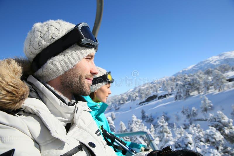 Pares de los esquiadores que montan en la telesilla imagenes de archivo