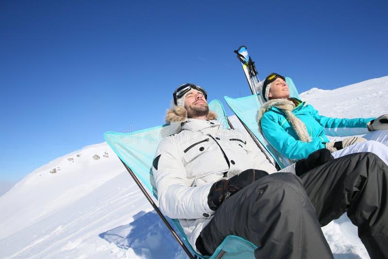 Pares de los esquiadores que toman tomar el sol de la rotura imágenes de archivo libres de regalías