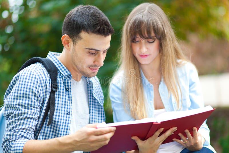 Pares de los estudiantes que leen un libro fotos de archivo libres de regalías