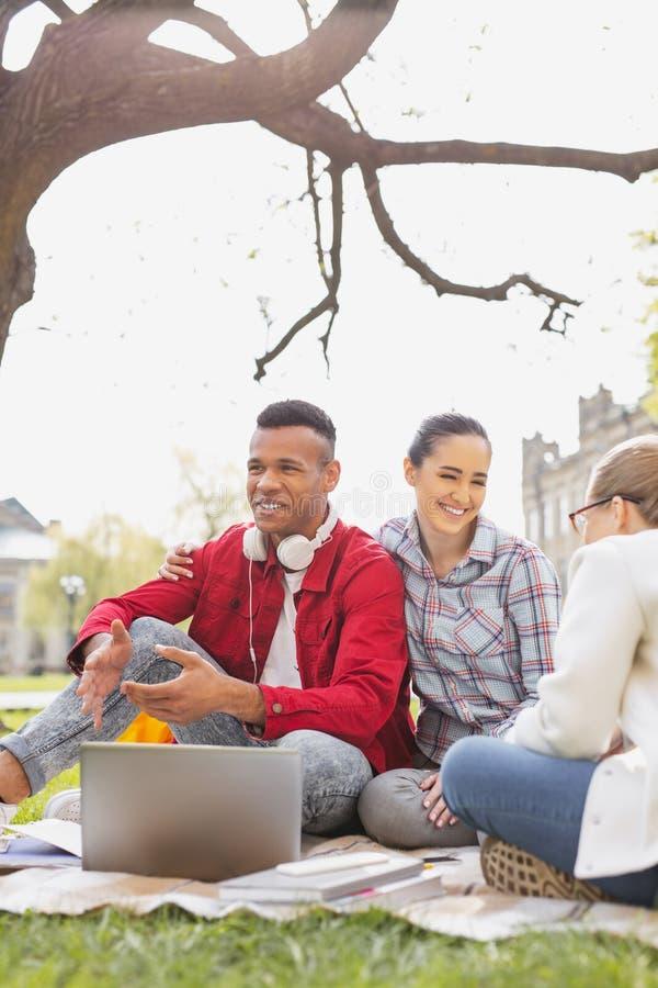 Pares de los estudiantes sonrientes que se sientan debajo del árbol imagen de archivo