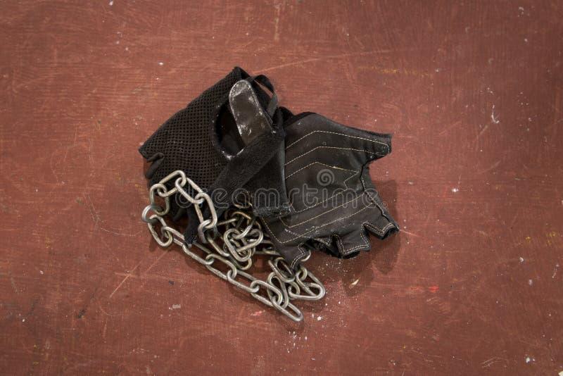 Pares de los guantes negros del levantamiento de pesas y de la aptitud, accesorio con la cadena de plata contra fondo rojo áspero fotos de archivo libres de regalías