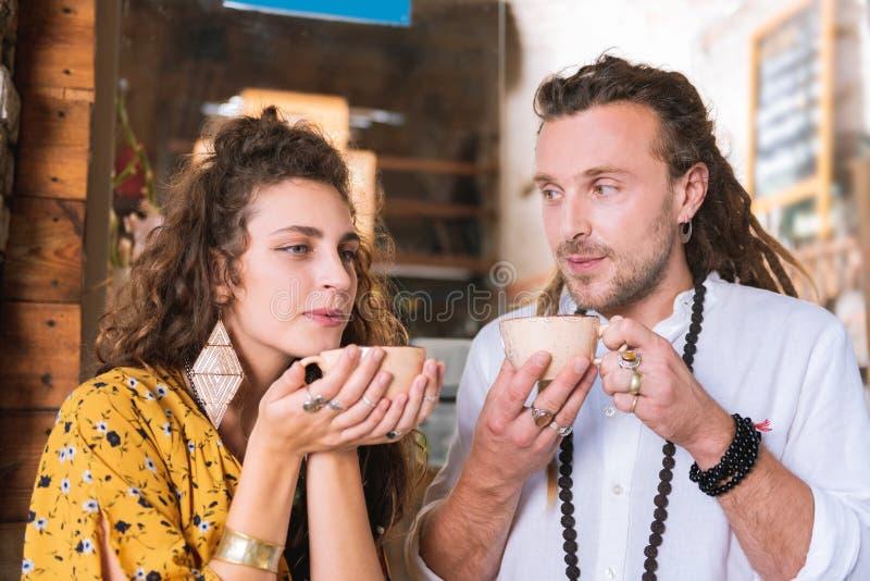 Pares de los hippies elegantes que beben té en su propio pequeño café foto de archivo
