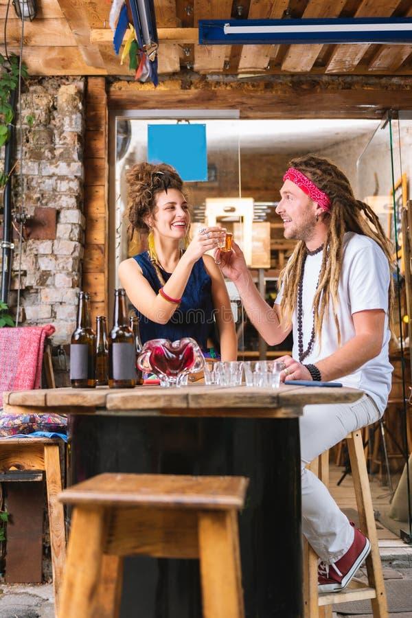 Pares de los hippies elegantes que sientan tequila y la cerveza de consumición fotos de archivo