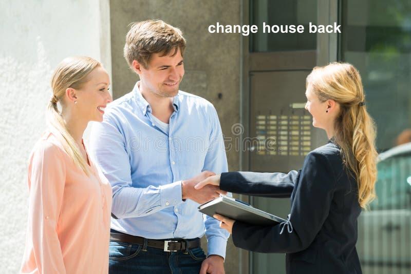 Pares de los jóvenes de Shaking Hands With del agente de la propiedad inmobiliaria fotografía de archivo libre de regalías