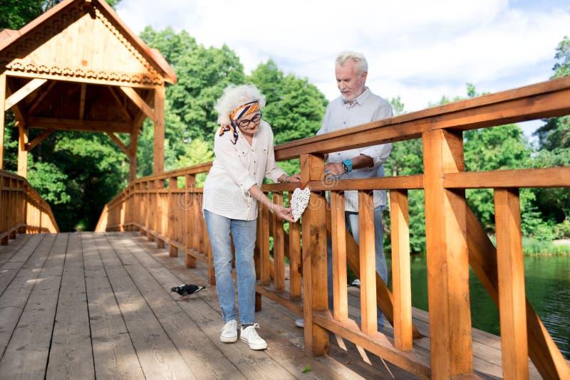 Pares de los pensionistas que muestran al mundo el corazón eterno de la ejecución del amor en el puente foto de archivo