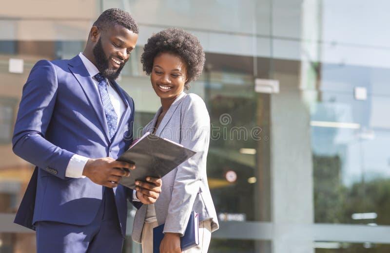 Pares de los socios comerciales afroamericanos que trabajan mientras que se coloca al aire libre imágenes de archivo libres de regalías