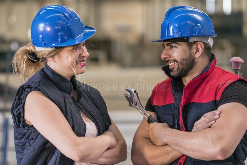 Pares de los trabajadores de construcción que hablan y que tienen una rotura imágenes de archivo libres de regalías