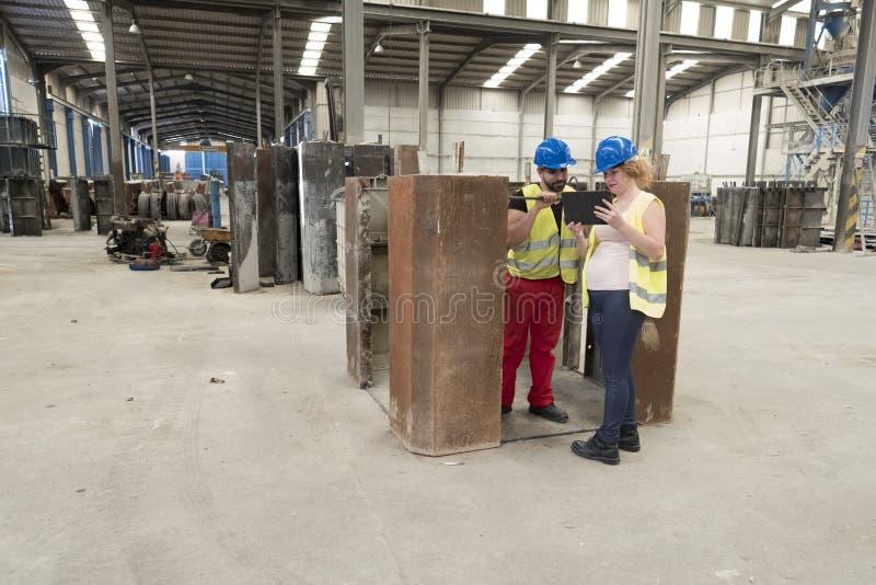 Pares de los trabajadores que miran la tableta en el edificio industrial fotografía de archivo libre de regalías