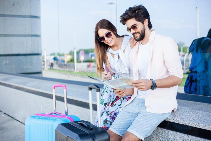 Pares de los turistas jovenes que se sientan delante de una terminal de aeropuerto y que miran el mapa foto de archivo