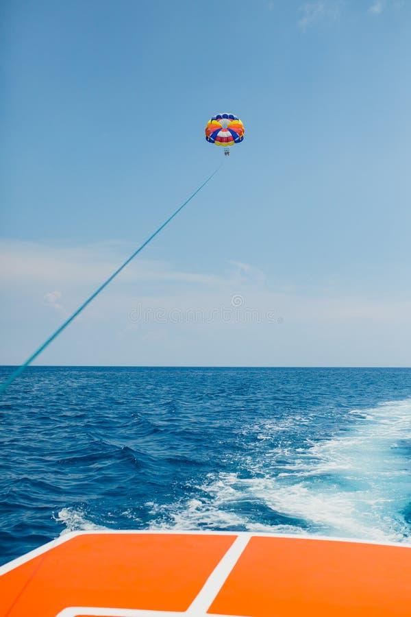 Pares de los turistas que vuelan en un paracaídas coloreado multi fotografía de archivo libre de regalías