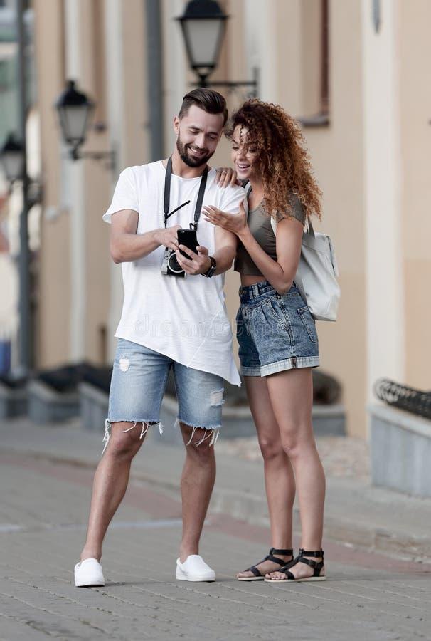 Pares de los turistas sonrientes felices que caminan alrededor de la ciudad foto de archivo libre de regalías