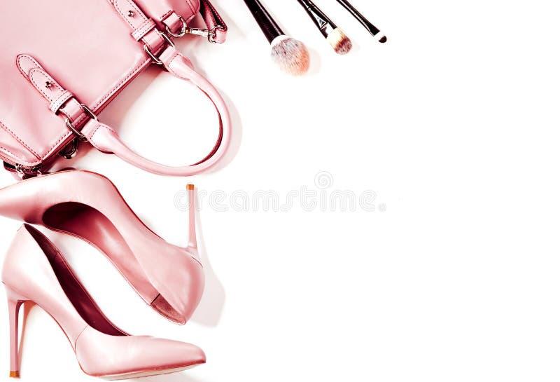 Pares de los zapatos de tacón alto de las mujeres desnudas beige con el bolso en una opinión superior del fondo blanco, endecha p fotografía de archivo