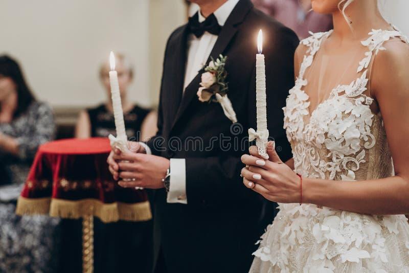 Pares de lujo de la boda que llevan a cabo velas con la luz durante traditi fotos de archivo