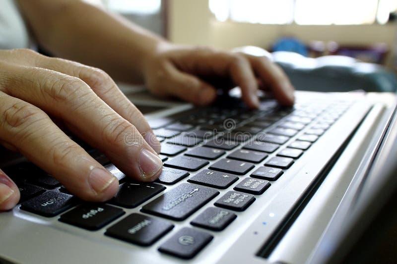 Pares de mãos em um teclado de computador fotos de stock
