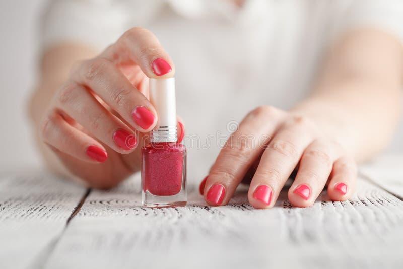 Pares de manos femeninas que abren la botella del esmalte de uñas imagenes de archivo