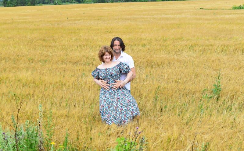 Pares de mediana edad cariñosos que se colocan en campo en verano fotografía de archivo libre de regalías