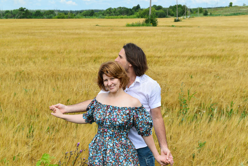 Pares de mediana edad cariñosos que se colocan en campo en verano fotos de archivo