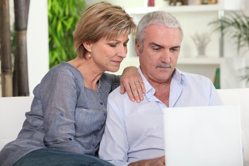 Pares de mediana edad con un ordenador imagenes de archivo