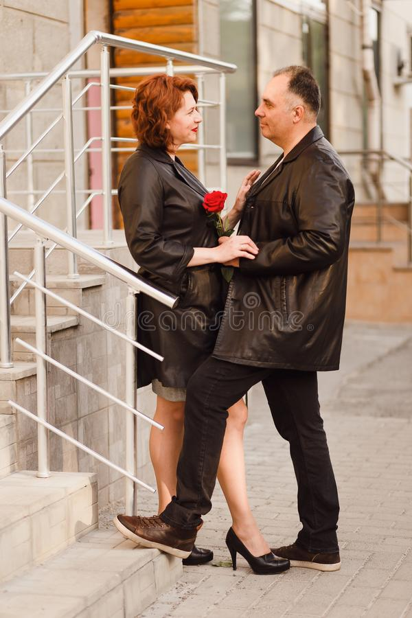 Pares de mediana edad en integral en una calle de la ciudad en el verano en la luz de la puesta del sol Un hombre y una mujer cin imagen de archivo