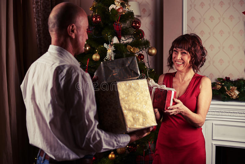 Pares de mediana edad que intercambian los regalos mientras que se coloca cerca de Christma foto de archivo