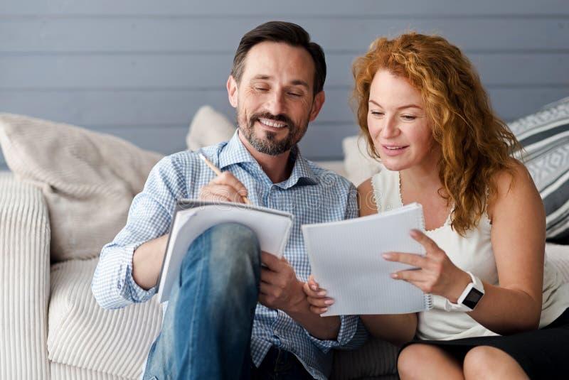 Pares de meia idade do homem e da mulher que fazem anotações imagem de stock