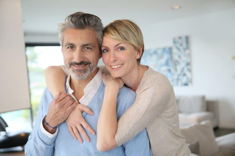 Pares de meia idade em casa que abraçam foto de stock royalty free