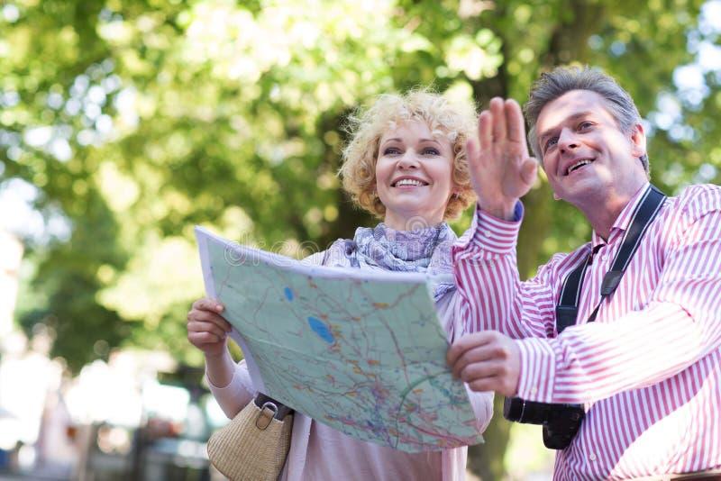 Pares de meia idade felizes que guardam o mapa na cidade imagens de stock